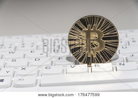 Shining gold metal BTC bitcoin coin on white computer keyboard.