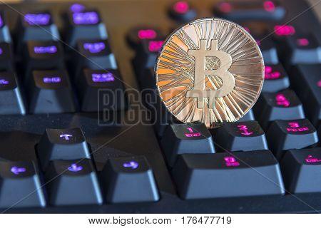 Shining gold metal BTC bitcoin coin on black computer keyboard.
