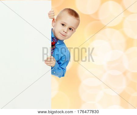 Beautiful little boy in a blue shirt and tie peeking from behind the banner.
