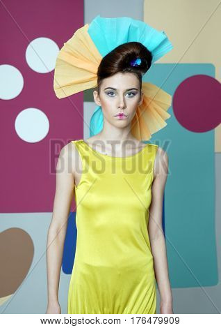 Portrait of attractive girl in bright eccentric outfit. Woman dressed in short dress with open shoulders and paper headdress. She looks at the camera, mouth closed. Color background: circles, rectangles