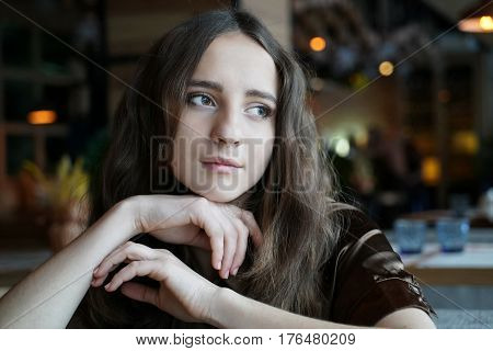 Lovely dark-haired girl sits in cafe. Macro shot. Beautiful young woman loneliness in coffee shop, thinking about something. Dark-brown eyes, natural make-up, healthy skin.