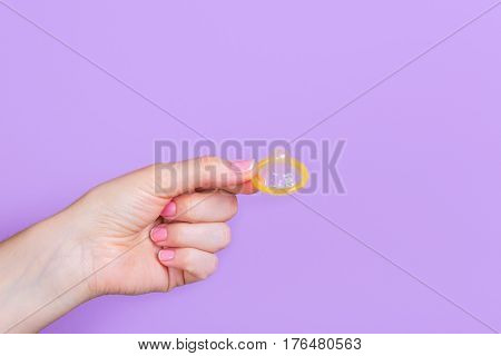 Hand holding a condom isolated on a purple background