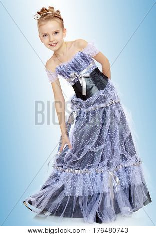Slender little girl , with beautiful hair on her head, elegant long Princess dress.The girl twisted to the side and keeps her hand on her knee.On the pale blue background.