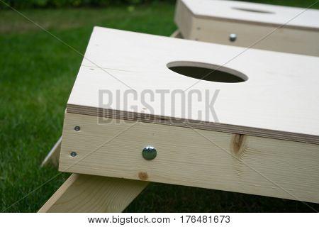 Close-up of wood cornhole board on grass