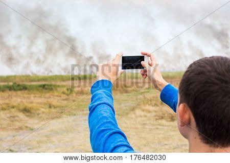 the person holding in hand cell phone with camera which he photographs the strongest fire and smoke in the wild nature