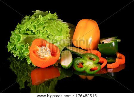 Fresh vegetables on a black background with reflection. Composition from lettuce leaves sweet paprika and cucumbers. A part of vegetables is cut on pieces and segments. Selective focus