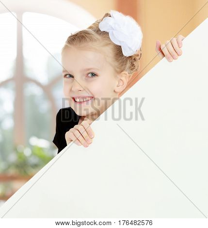 Beautiful little blonde girl dressed in a white short dress with black sleeves and a black belt.The girl peeks out from behind white banner. Close-up. In a room with a large semi-circular window.
