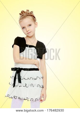 Beautiful little blonde girl dressed in a white short dress with black sleeves and a black belt.Girl poses for the camera.Close-up.On a yellow gradient background.