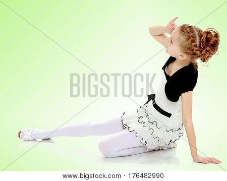 Beautiful little blonde girl dressed in a white short dress with black sleeves and a black belt.Girl sitting on the floor leaning on hand and looking to the side.