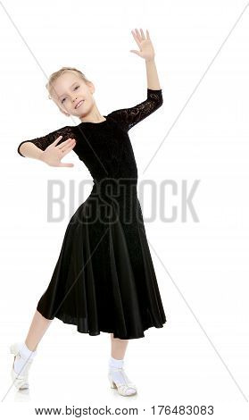 The slender little blonde girl dancer in the long dress of black color made specifically for performing .Girl graceful curves of the body.Isolated on white background.