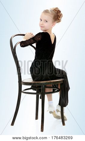 The slender little blonde girl dancer in the long dress of black color made specifically for performing .Girl sitting on an old Viennese chair and looking at the camera over his shoulder.On the pale blue background.