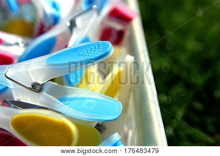 Closeup Of Brightly Colored Clothespins In A Container On Grass,  With Selective Focus