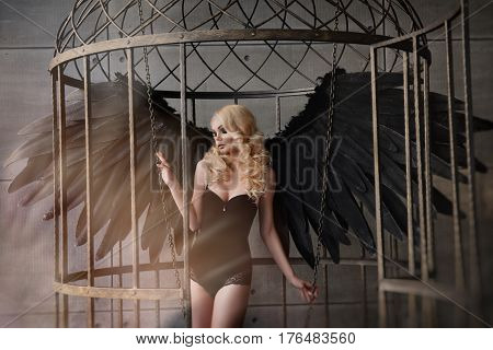 Young sexual blond woman with black wings in a cage. Angel, mysticism