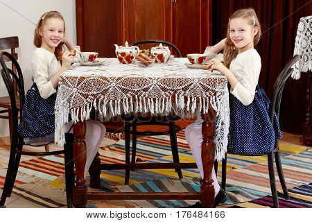Cute little girls twins drinking tea at an antique table with a lace tablecloth.Retro style.
