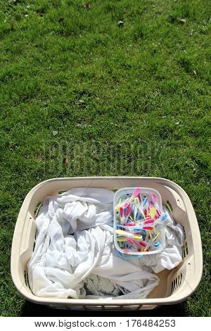 Laundry Basket Full Of Laundry Ready To Be Hung Out With Colourful Clothes Pegs