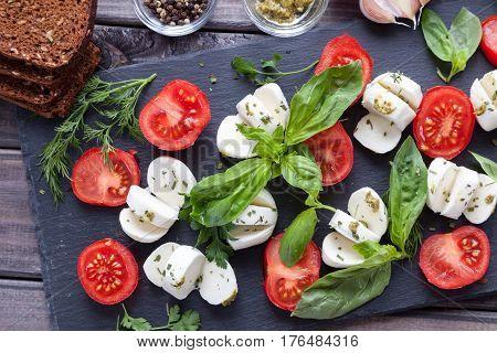 Cherry tomatoes, mozzarella cheese, basil, pesto sauce, dark rye grain bread and spices on black slate stone chalkboard. Italian traditional caprese salad ingredients. Mediterranean food. Top view