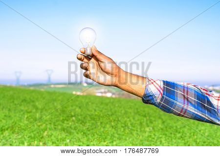 Man hand holding glowing light bulb on green environment background - Shining lamp rising from african american farmer arm in wheat field - Concept of modern clean energy and people creative ideas