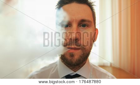 Young Funny White Businessman With Beard And Mustache Emits Puff Of Steam From The Electronic Cigare
