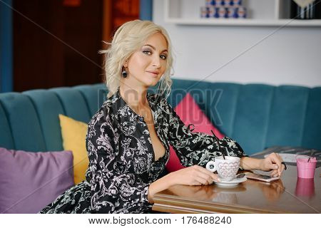beautiful girl waiting for boyfriend in cafe. romantic date in a cafe. attractive girl sits at a table with a cup of coffee