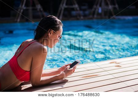 Beautiful woman leaning on poolside and typing a text message on cellphone.