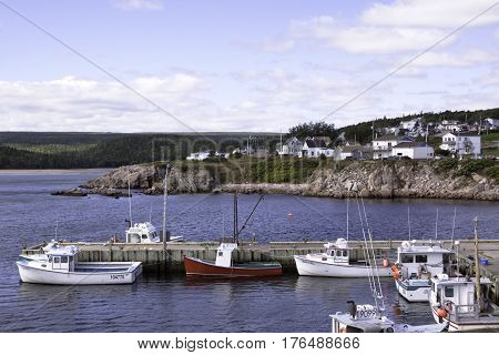 Highlands National Park, Nova Scotia, September 24, 2015 -- A short pier is filled with small fishing boats in the Gulf of St. Lawrence with homes on a rock face in the background in Cape Breton Highlands National Park, Nova Scotia on a beautiful bright c