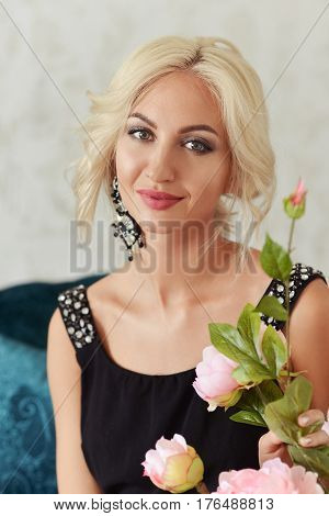 Blonde woman in a black dress in a room with a bouquet of flowers