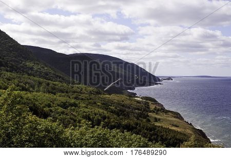 Wide view of the beautiful landscape along the scenic winding road that goes through the Cape Breton Highlands National Park, Nova Scotia and the Gulf of St. Lawrence on a beautiful bright cloud filled sunny day in September.