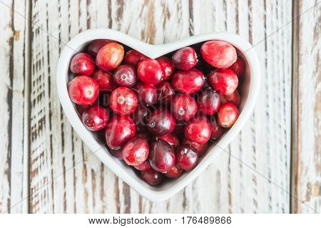 Fresh cranberries in a saucer on a wooden background
