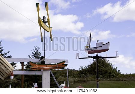 Small colorful wooden novelty boats are displayed against the blue sky in Cape Breton Highlands National Park, Nova Scotia on a beautiful bright cloud filled sunny day in September.