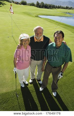 Senior couple with instructor on golf course, smiling, (portrait), (elevated view)