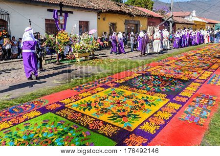 Antigua, Guatemala - March 25 2016: Locals reenact biblical scenes with processions walking over handmade dyed sawdust carpets on Good Friday in colonial town with most famous Holy Week celebrations in Latin America.