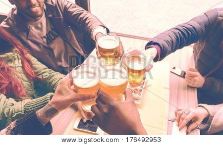 Friends cheering with beer glasses sitting around cafe bar table - Group of multiracial people toasting and clinking drinks at each others health inside pub