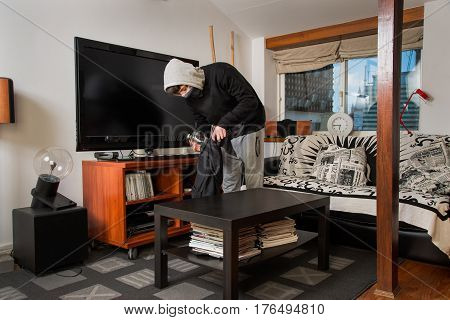 burglar robbing a house. Burglar stealing stuff in a living room