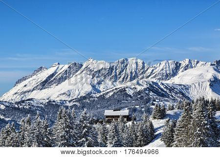 Image of a chalet located at the base of an Alpine peaks chaine close to Mont Blanc Massif.