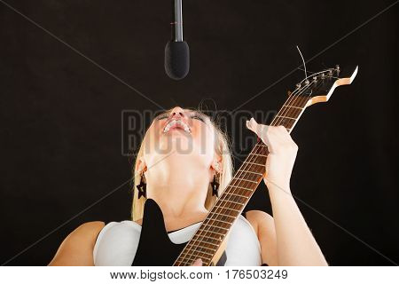Music singing concept. Musically talented woman playing on electric guitar and singing in studio black background