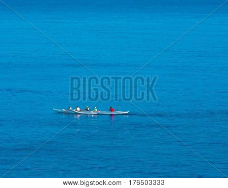 Two Kayak boats race in the Pacific Ocean in the early morning