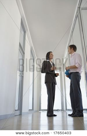 Two Businesspeople Talking in Corridor, low angle view.