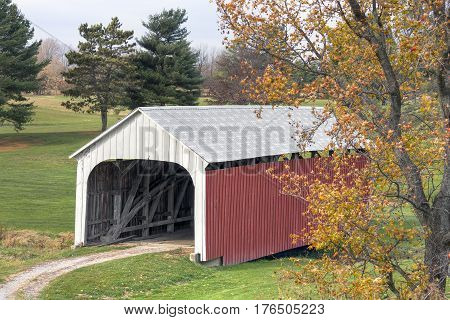 Built in 1907 the Catlin Covered Bridge now crosses Bill Diddle Creek near Rockville in rural Parke County Indiana seen here with a colorful autumn sweet gum tree in the foreground.