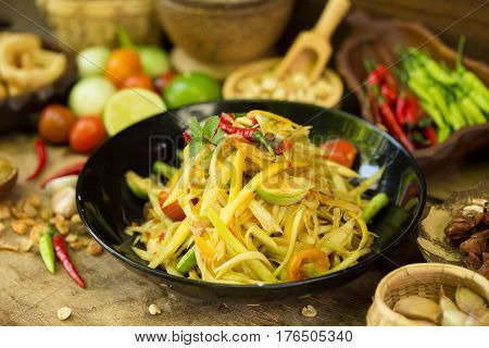 kitchen table with spicy papaya salad and ingredient food Thai national food concept of hot asian food.
