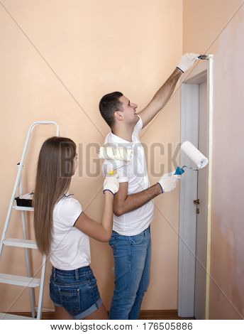 Portrait of happy cheerful couple painting interior wall of new house or flat. She is painting him. He is holding roller for painting and brush.