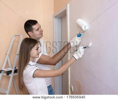 Portrait of happy young couple painting interior wall of new house or flat. She is holding brush and He is holding roller for painting.