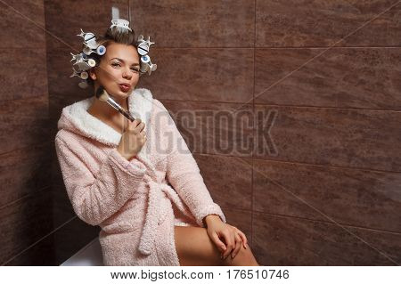 Young attractive housewife in the bathroom. A girl in a bathrobe and curlers doing morning makeup. Makeup Brush. Good morning. Flirting. poster