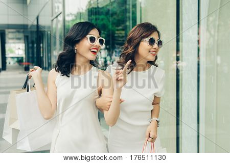 Shopaholic friends with shopping bags walking on street at the mall