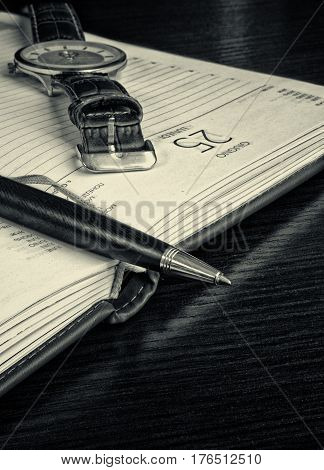 Pen and watch close up on an open notebook. The notebook lies on a table. Vertical format. Indoors. Without people. Мonochrome. Photo.