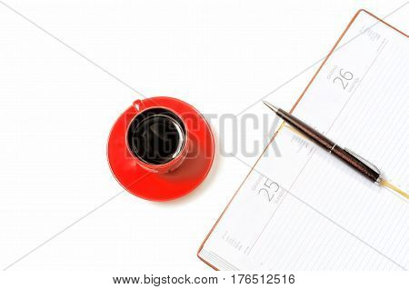 Open notebook and cup of coffee on a white background from above. On a notebook the ball-point pen lies. I will make a look. Working space. Indoors. Color. Horizontal format. Photo.
