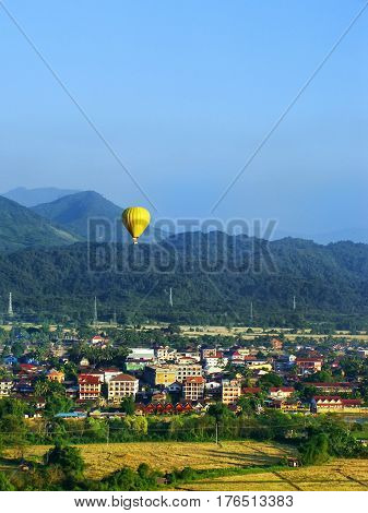 Hot air balloon flying above Vang Vieng town Vientiane Province Laos. Vang Vieng is a popular destination for adventure tourism in a limestone karst landscape.