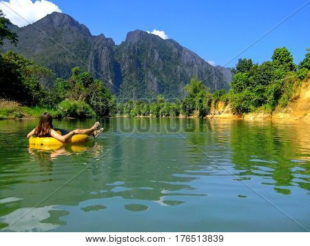 Tourist going down Nam Song River in a tube surrounded by karst scenery in Vang Vieng Laos. Tubing is a popular tourist activity in Vang Vieng.