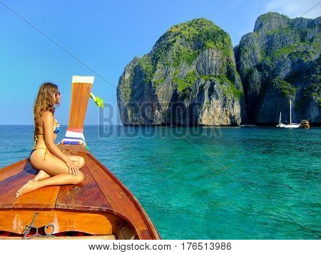Young woman sitting at the front of longtail boat in Maya Bay on Phi Phi Leh Island Krabi Province Thailand. Phi Phi Leh is part of Mu Ko Phi Phi National Park.