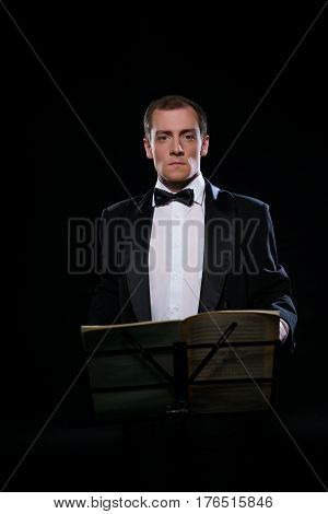 Young smart orchestra conductor in black tuxedo and bow-tie posing alone by the music stand in dark studio