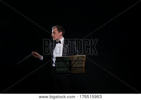 Young smart orchestra conductor in black tuxedo and bow-tie posing alone by the music stand with conductor s stick in dark studio
